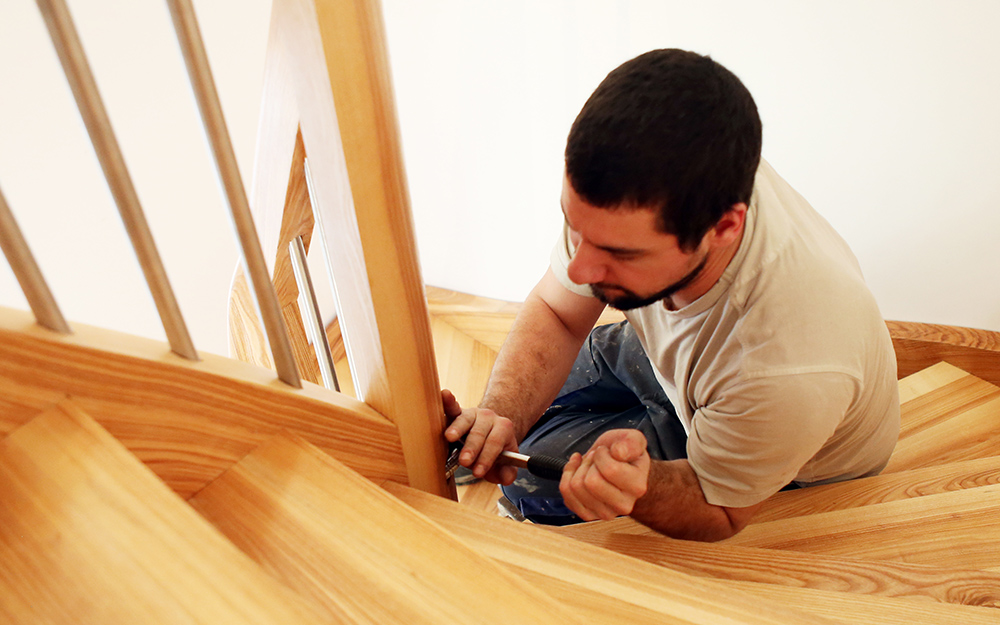 a man securing the handrail to a newly built staircase