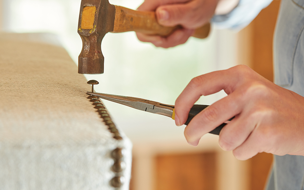 A person using a hammer to fasten fabric with upholstery tacks.