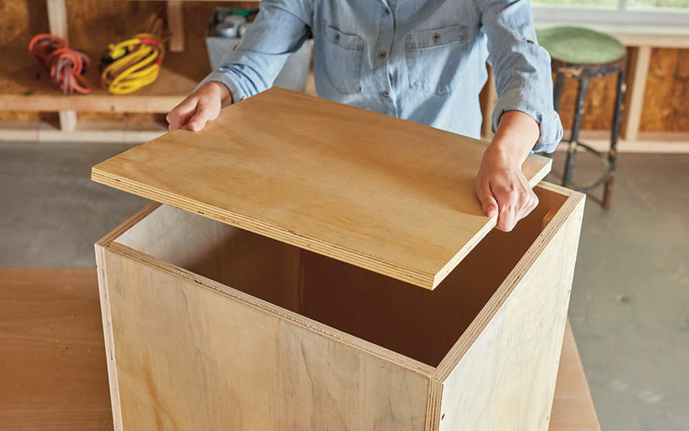 A person assembling pieces of plywood for a storage ottoman.