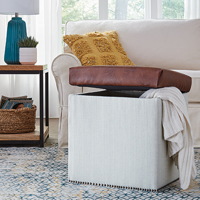 An upholstered storage ottoman in front of a sofa.