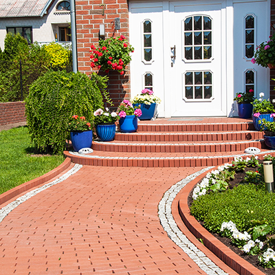 A brick walkway in a lawn leading to the entrance to a home.