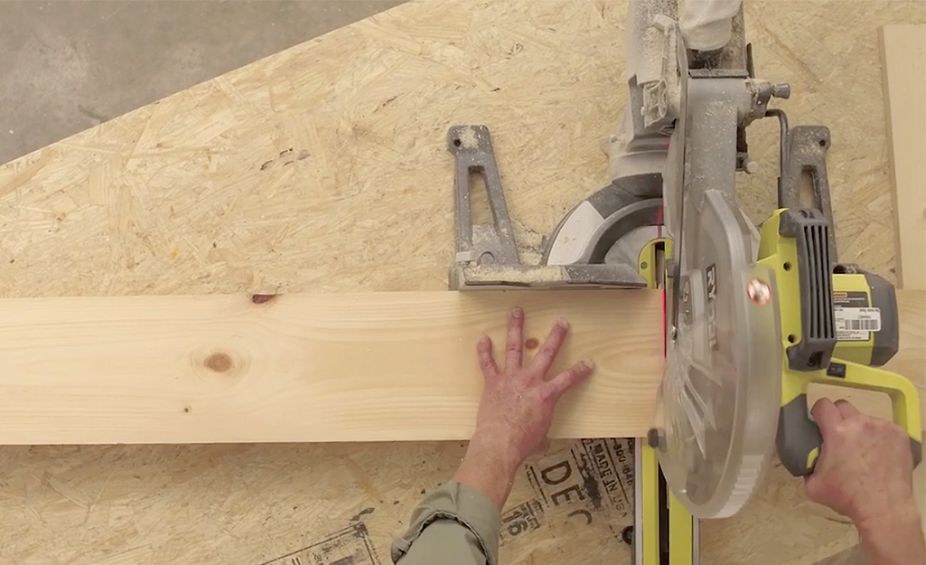 A man uses a circular saw to cut the lumber to build a wooden bed frame