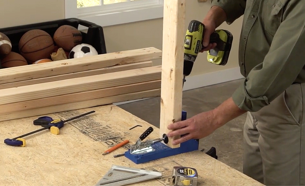 A man uses a jig to create pocket holes in the pieces of the wooden bed frame