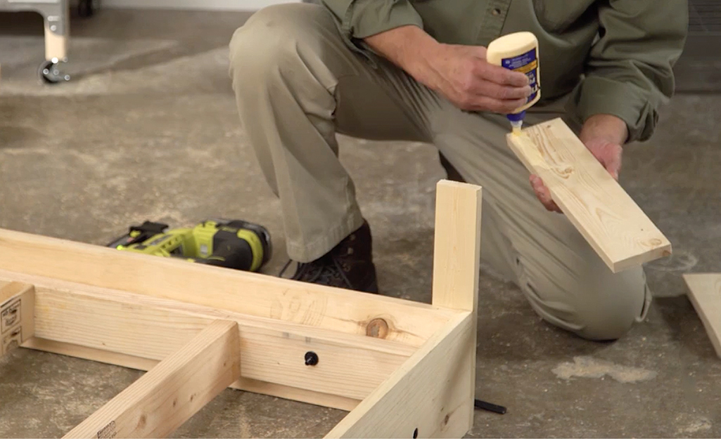 A man applies wood glue to the inner surface of the bed's legs before nailing them onto the frame