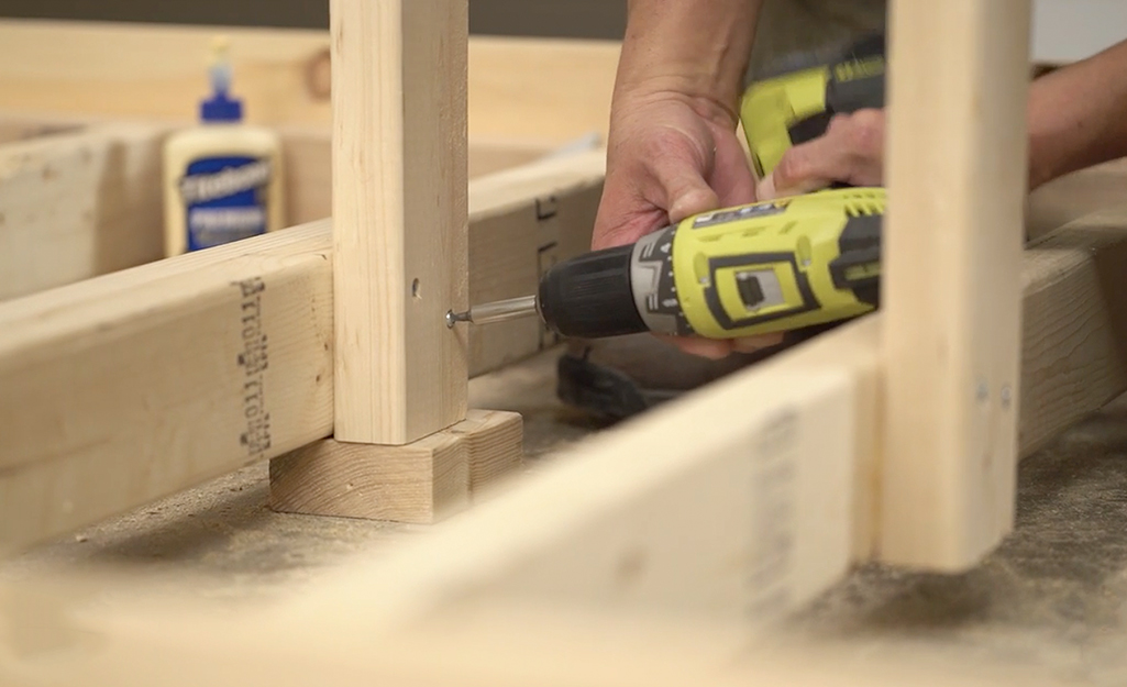A man adds center supports to the middle of the wooden bed frame's cross braces