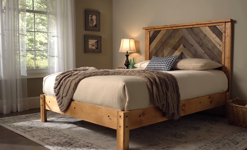 The completed wooden bed frame is shown with bedding and a matching wooden headboard.