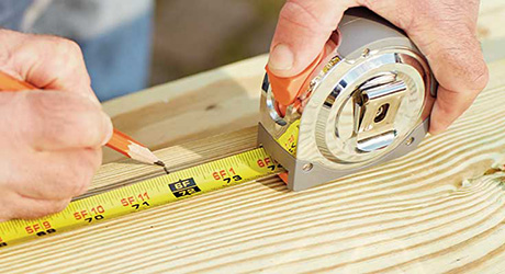 A person measuring and marking wood.