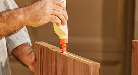 A person spreading wood glue on the edge of a board.
