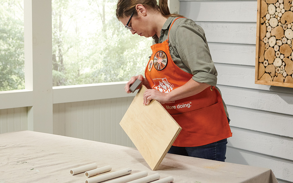 A Home Depot Associate sands the edges of a plywood board for a DIY crate table.