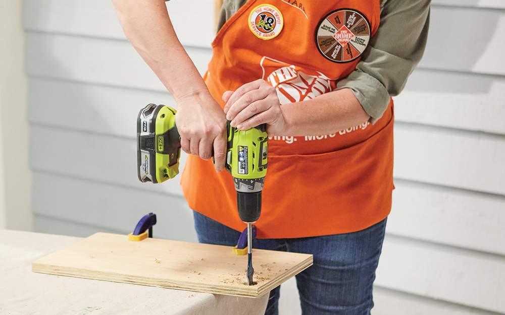 A Home Depot Associate drills holes into a board for a DIY crate end table.