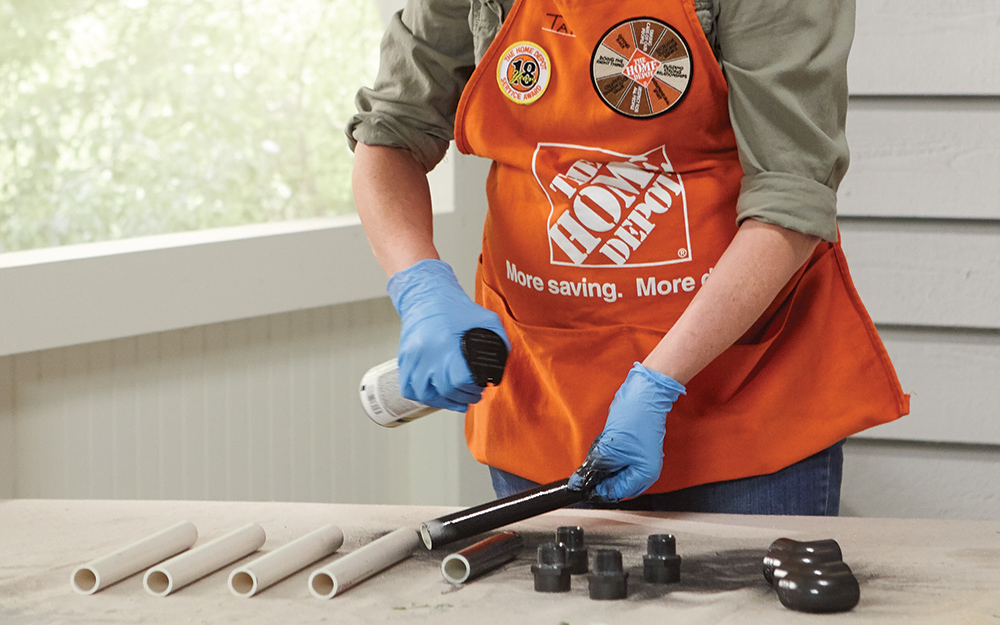 A Home Depot Associate spray paints the PVC leg pieces for a DIY crate table.