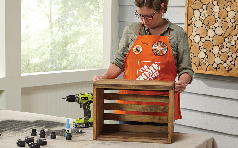A Home Depot Associate attached bottom board to wood crate using wood screws.