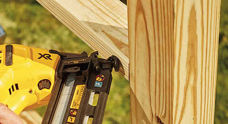 Someone using a nailer to attach studs to a wooden post