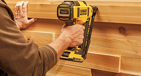 A person attaching wooden boards with a nail gun
