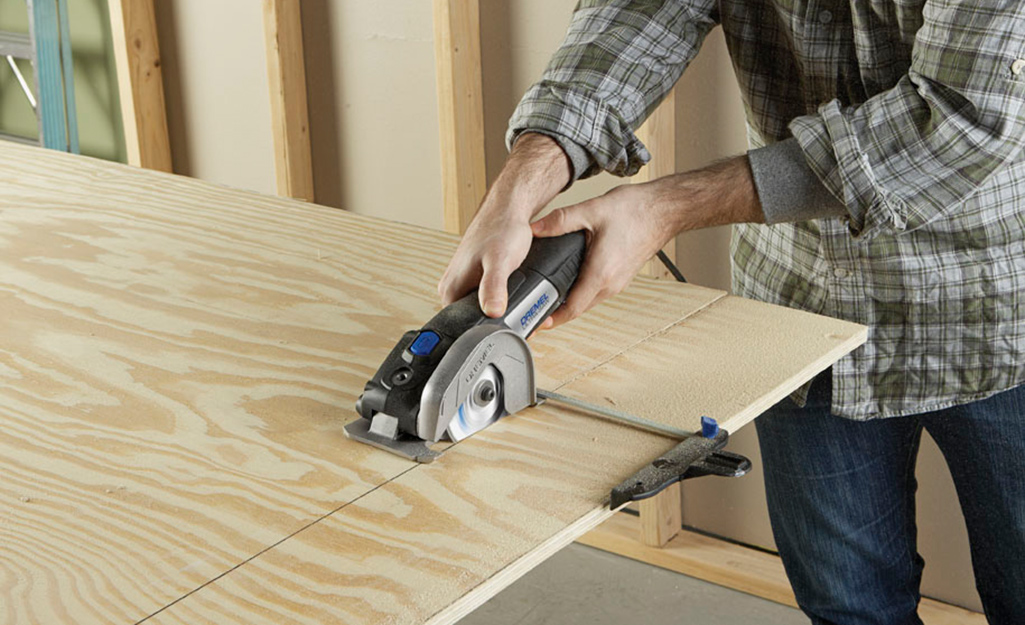 A person cutting plywood for utility shelves.