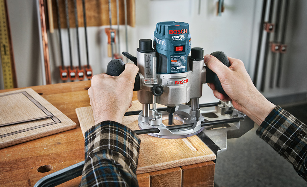 A person using a router to cut plywood for utility shelves.
