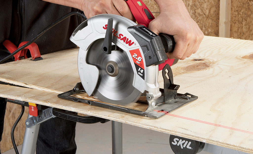 A person using a saw to cut a thin piece of plywood.