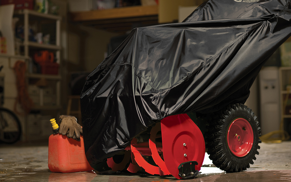 A snow blower with a cover on it sitting in a garage.