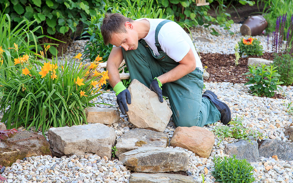 A man setting large stones into a landscape.