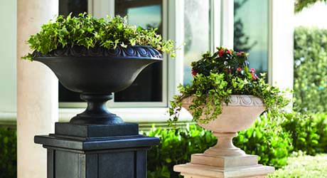 Two urn-style planters on a porch that have been planted with greenery, flowers and spiller plants.