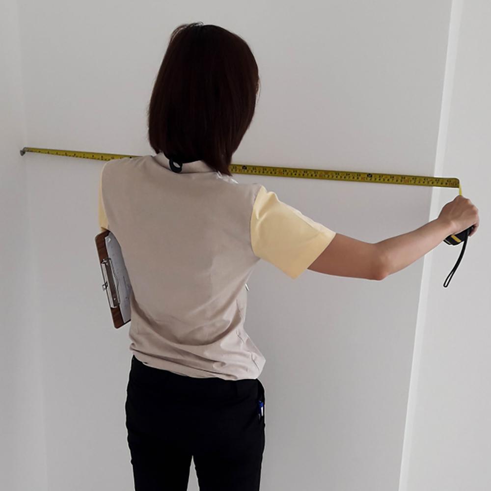 A person measuring a wall.
