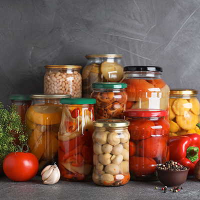 An arrangement of jars full of canned fruits and vegetables.