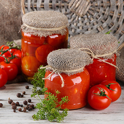 Jars of canned tomatoes and sprigs of herbs on a countertop.