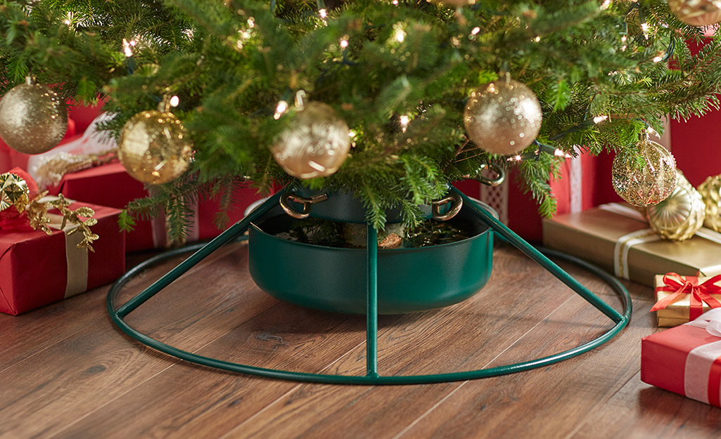 A green Christmas tree base with a tree in it.