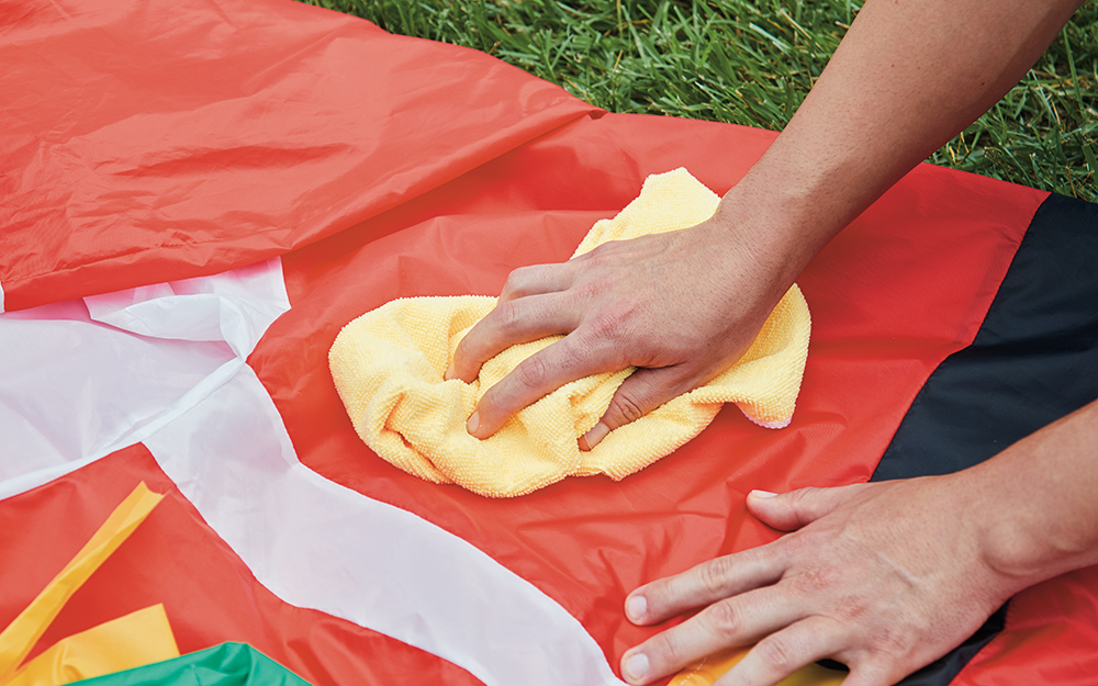 Someone wiping and cleaning an inflatable with a soft cloth.