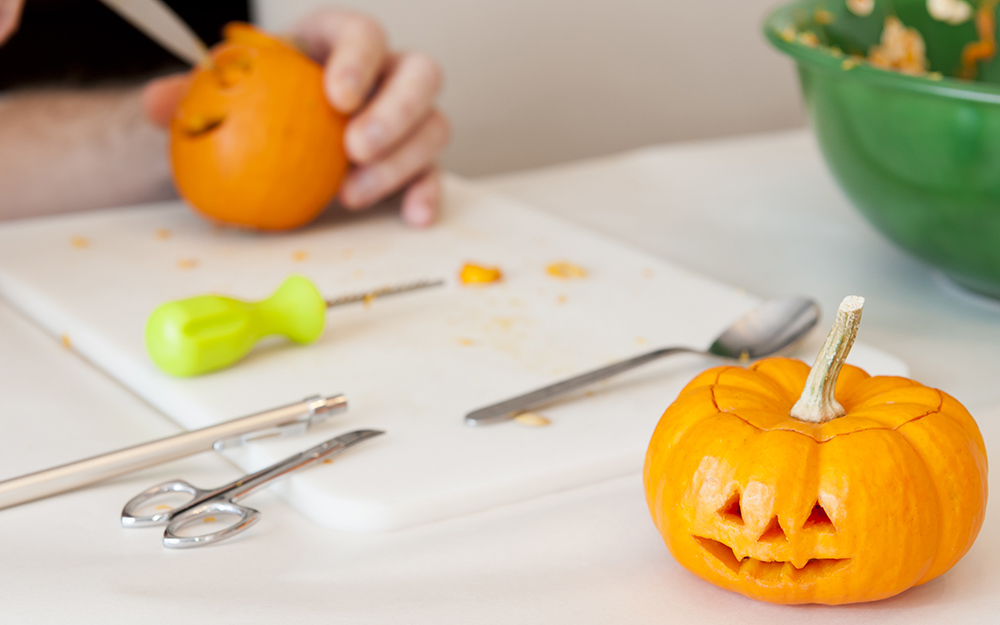Small pumpkins being carved at a carving station.