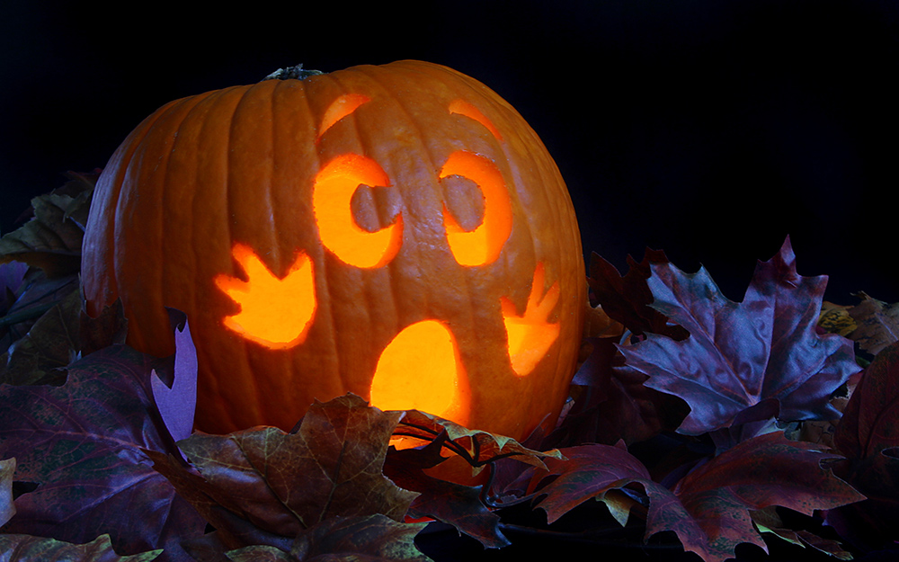A scared cartoon looking face carved into a glowing pumpkin.