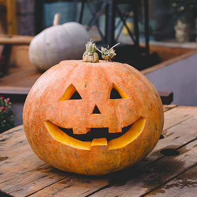 Someone applying petroleum jelly to the smile of a jack-o'-lantern.