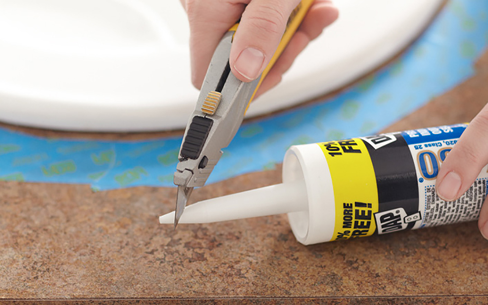 person cutting the tip off the nozzle of a caulk tube