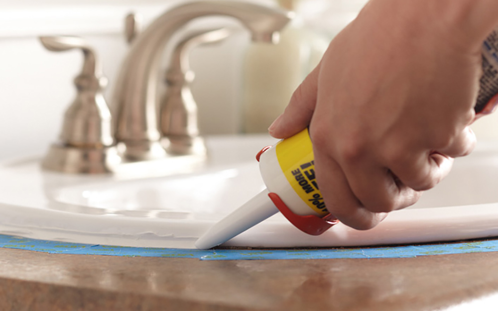 person applying new caulk around bathroom sink