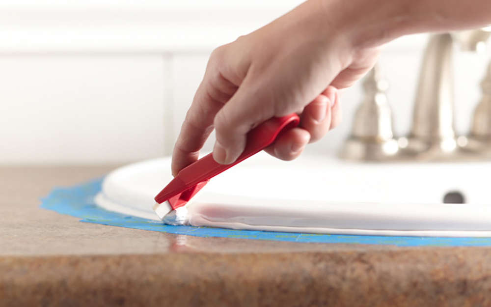 How to Caulk - Person smoothing new caulk around bathroom sink