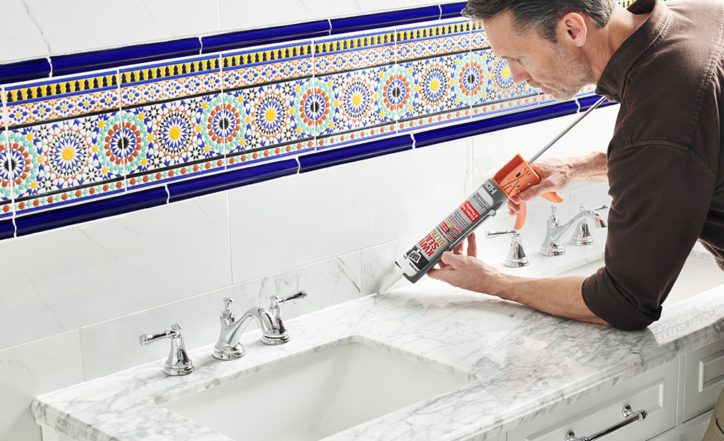A person using a caulk gun to apply caulk between a vanity and wall.