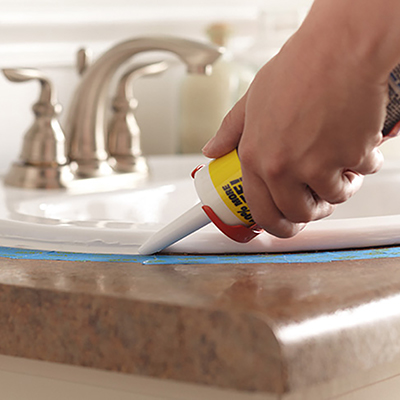 person applying caulk around bathroom sink