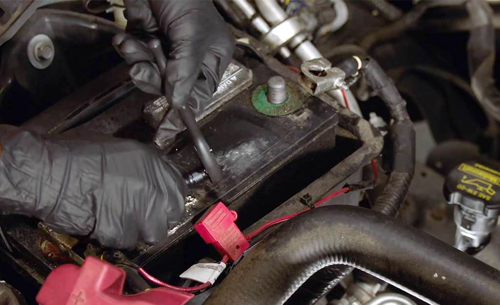 Two hands wearing gloves detaching cables from a car battery.