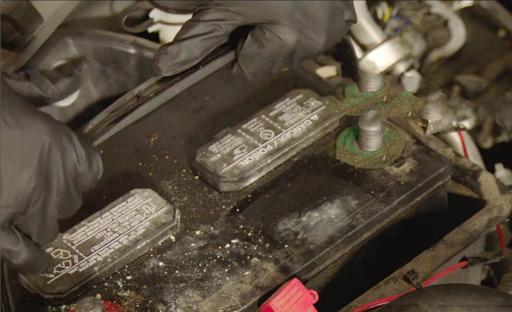 Two hands removing a car battery.