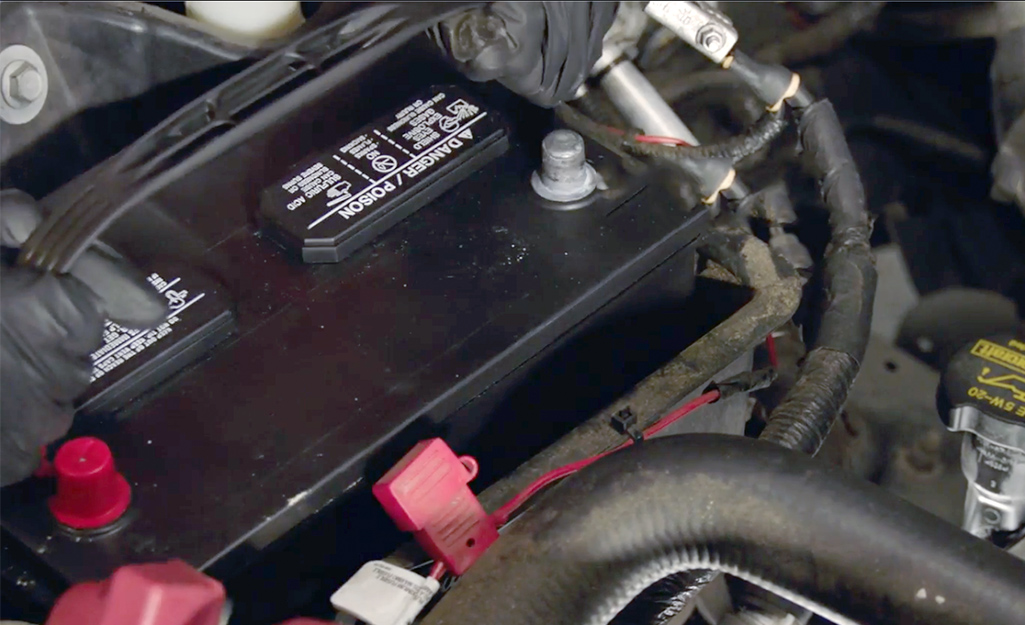 Two hands lowering a new car battery into place.