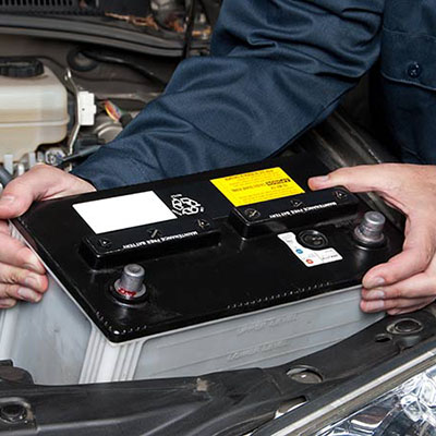 Person holding a car battery above a car engine.