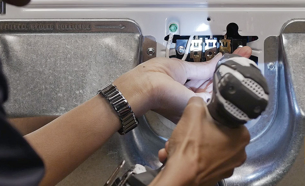A person using a power drill to loosen screws inside a dryer's access panel.