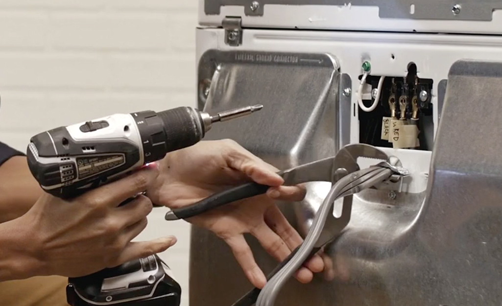 A person uses pliers to hold a dryer cord strain relief bracket.