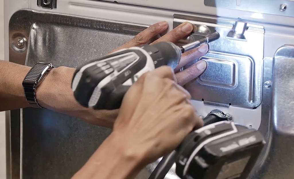 A person using a drill to attach the access panel to the back of a dryer.