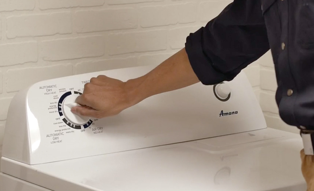 A person adjusting the settings knob on the front of a dryer.
