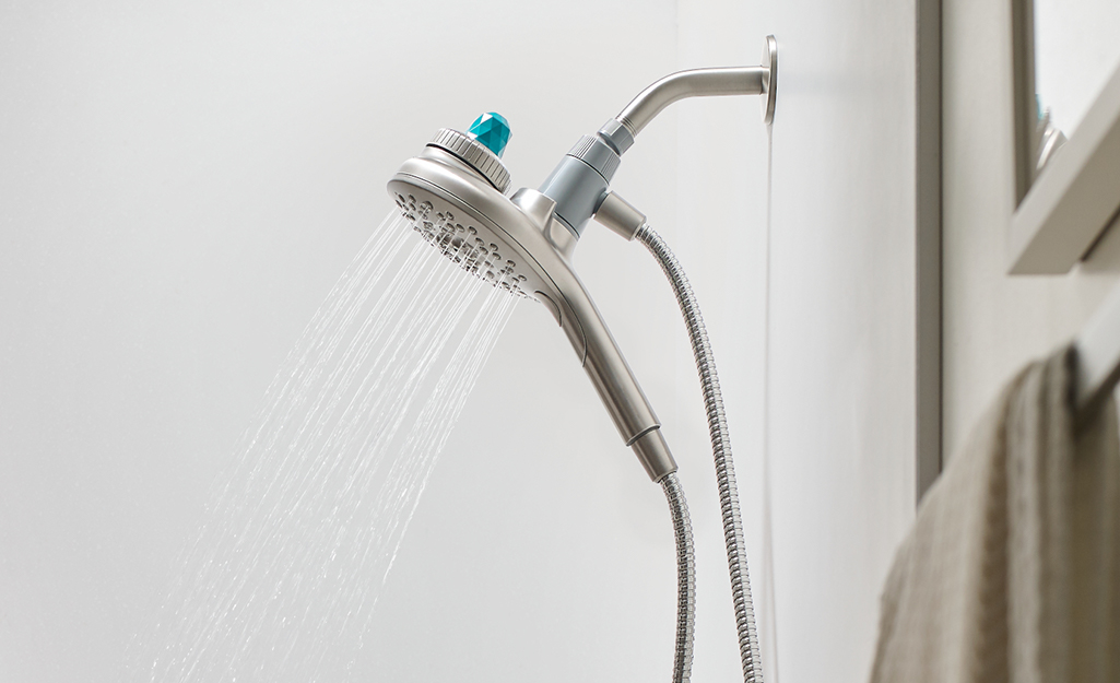A hand held shower head in a shower with water spraying out.