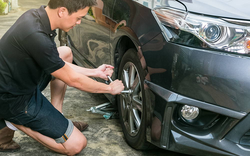 A man removing the lug nuts from the wheel of a car.