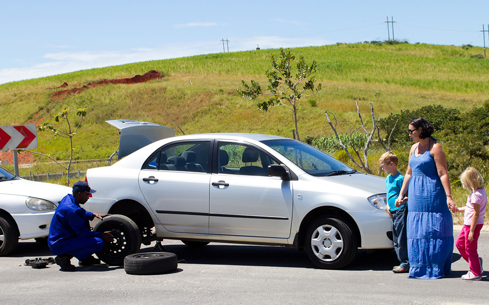 A family waits while a service person performs roadside assistance.