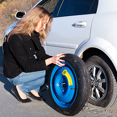 A woman changing a tire on a white car.