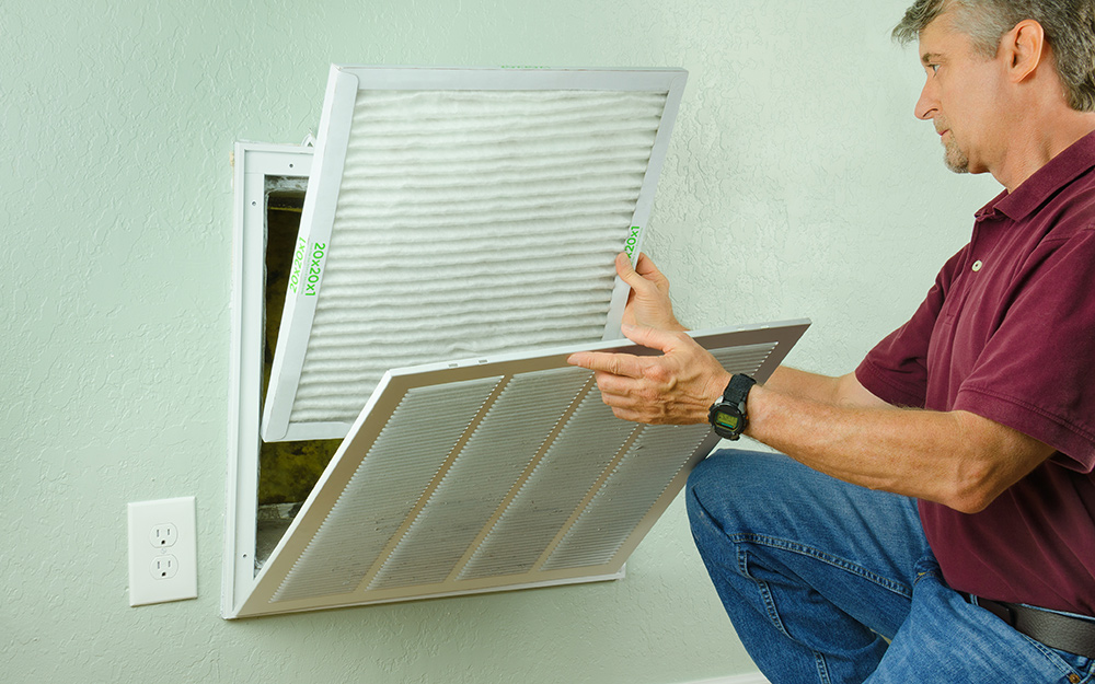 A person removing an air filter from a wall vent.